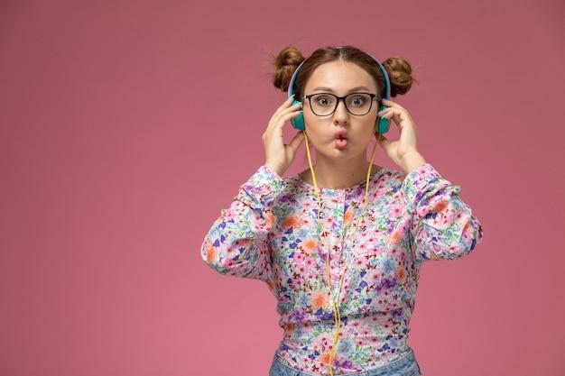 Вид спереди молодая женщина в рубашке с цветочным дизайном и синих джинсах, слушающая музыку в наушниках на розовом фоне