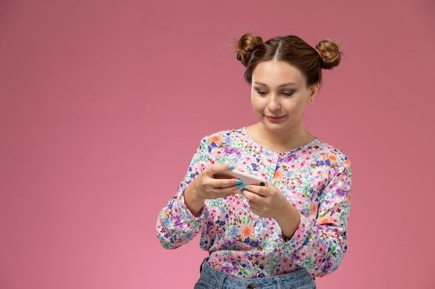 Вид спереди молодой женщины в рубашке с цветочным дизайном и синих джинсах, играющей в игры по телефону на розовом фоне