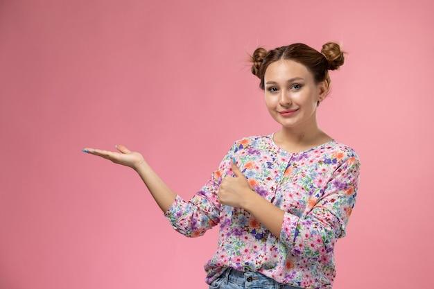 花の正面の若い女性のデザインのシャツとブルージーンズは明るい背景にわずかな笑顔でポーズ