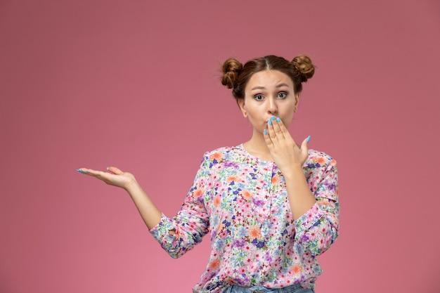 花の正面の若い女性のデザインのシャツとブルージーンズにピンクの背景に覆われた口でポーズ