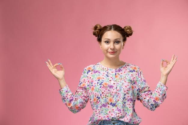 正面の若い女性の花のデザインのシャツとブルージーンズの笑顔とピンクの背景に瞑想のポーズ