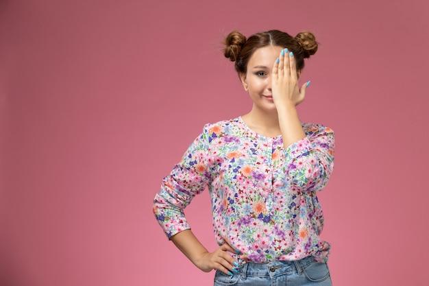 Вид спереди молодая женщина в рубашке с цветочным дизайном и синих джинсах, улыбаясь, закрывая одну сторону лица на розовом фоне