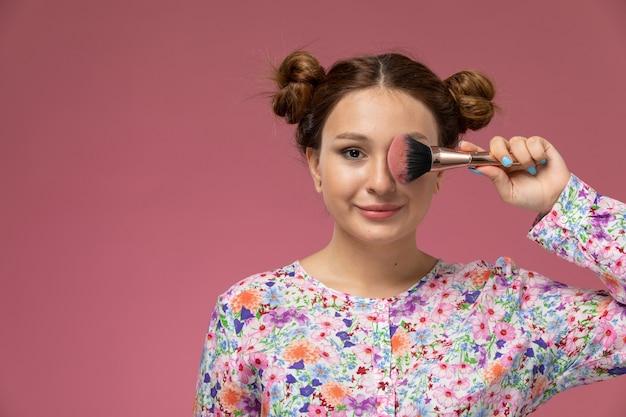 花の正面の若い女性のデザインのシャツとピンクの背景に笑みを浮かべて持株化粧筆のブルージーンズ