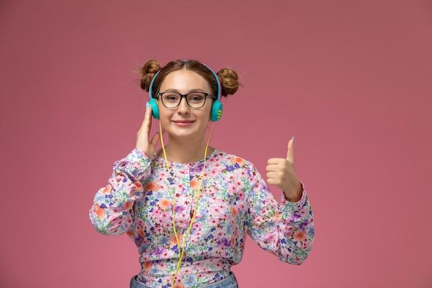 Вид спереди молодая женщина в рубашке с цветочным дизайном и синих джинсах улыбается, слушая музыку на розовом фоне