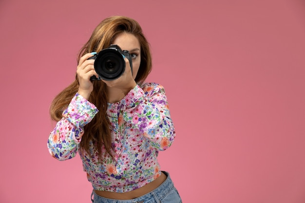 花の正面の若い女性のデザインのシャツとブルージーンズピンクの背景にカメラで写真を撮って笑って