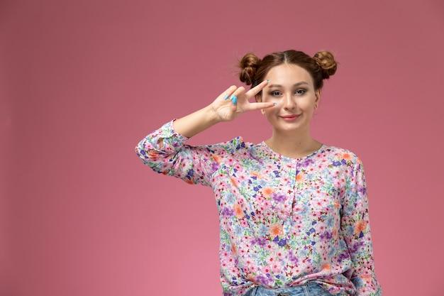 Вид спереди молодая женщина в рубашке с цветочным дизайном и синих джинсах, улыбаясь с милым выражением лица на розовом фоне