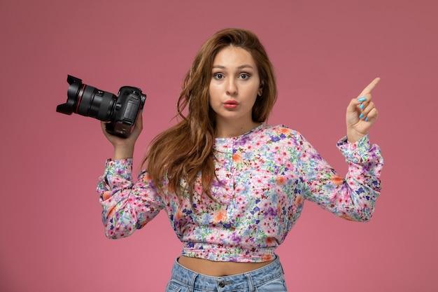 분홍색 배경에 카메라로 사진을 찍는 꽃 디자인 셔츠와 청바지에 전면보기 젊은 여성