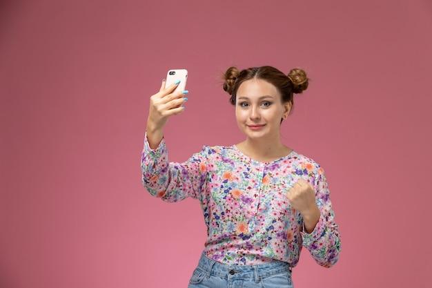 Вид спереди молодая женщина в рубашке с цветочным дизайном и синих джинсах, делающая селфи с улыбкой на розовом фоне