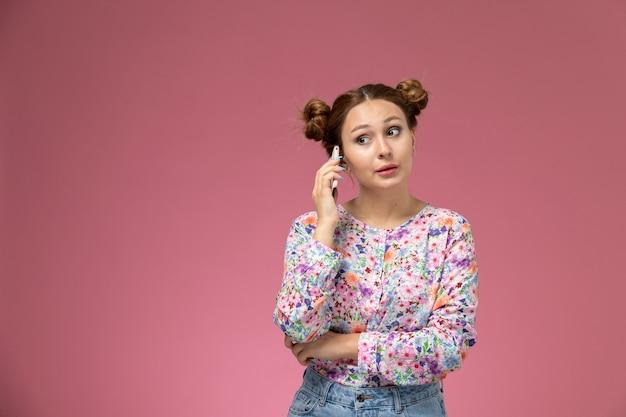 Вид спереди молодая женщина в цветочной рубашке и синих джинсах разговаривает по телефону на розовом фоне