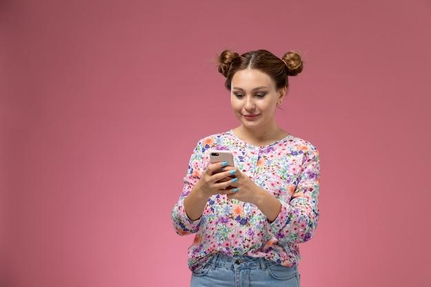 Вид спереди молодая женщина в рубашке с цветочным дизайном и синих джинсах, использующая телефон на розовом фоне