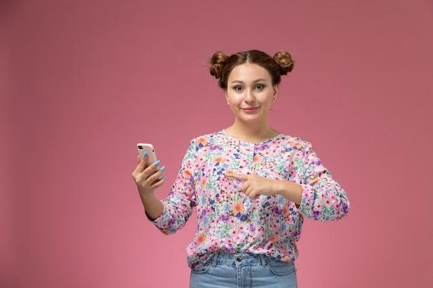 Вид спереди молодая женщина в рубашке с цветочным дизайном и синих джинсах, использующая телефон, улыбаясь на розовом фоне
