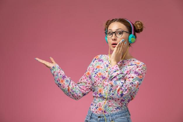 Вид спереди молодая женщина в рубашке с цветочным дизайном и синих джинсах в наушниках, слушающая музыку на розовом фоне