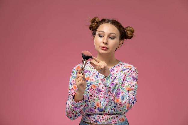 ピンクの背景に化粧ブラシを保持している花柄のシャツの正面若い女性
