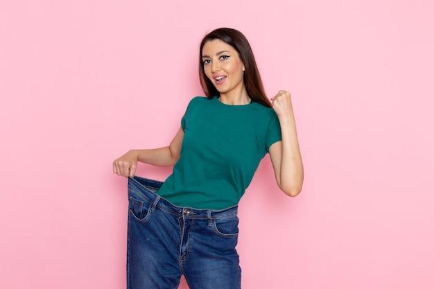 밝은 분홍색 벽 허리 스포츠 운동 운동 아름다움 슬림 운동 선수 여성에 그녀의 허리를 검사하는 녹색 티셔츠에 전면보기 젊은 여성