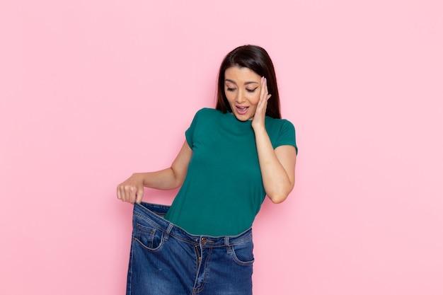 분홍색 벽 허리 스포츠 운동 운동 아름다움 슬림 여성에 그녀의 허리를 검사하는 녹색 티셔츠에 전면보기 젊은 여성