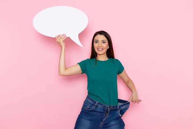 분홍색 벽 허리 스포츠 운동 운동 아름다움 슬림 운동 선수에 거대한 흰색 기호를 들고 녹색 티셔츠에 전면보기 젊은 여성