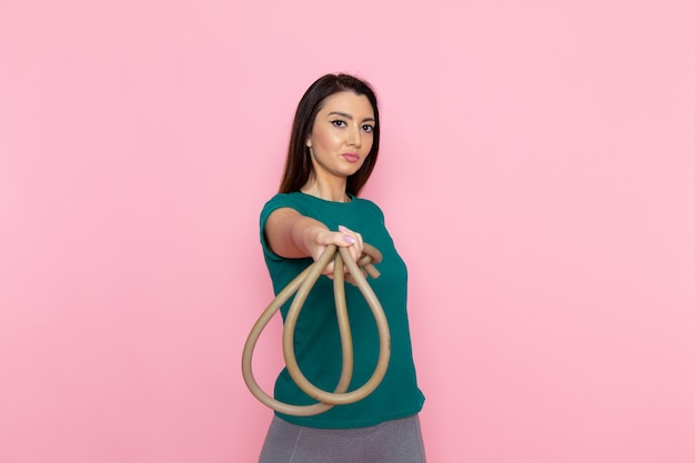 분홍색 벽 허리 스포츠 운동 운동 아름다움 슬림 운동 선수에 스포츠를위한 녹색 티셔츠 지주 로프에 전면보기 젊은 여성