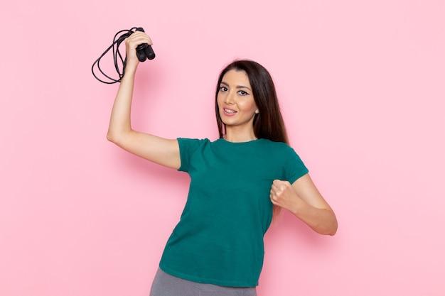 Вид спереди молодая женщина в зеленой футболке, держащая скакалку на светло-розовой стене, тренировка талии, красота стройная, женский спорт