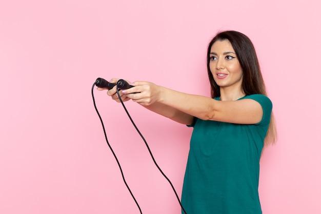 Вид спереди молодая женщина в зеленой футболке, держащая скакалку на светло-розовой стене, талии, спортивные упражнения, тренировки, красота, стройная женщина