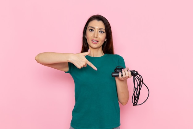 ピンクの壁に縄跳びを保持している緑のtシャツの正面図若い女性ウエストスポーツ運動トレーニング美容スリムアスリート