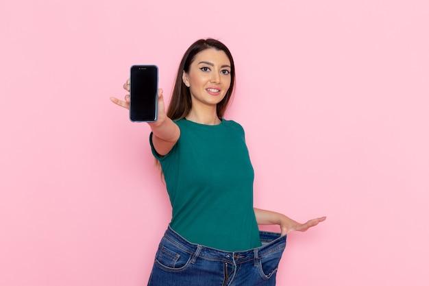 Вид спереди молодая женщина в зеленой футболке, держащая смартфон на светло-розовой стене, упражнения на талии, тренировка, красота, стройность, женский спорт