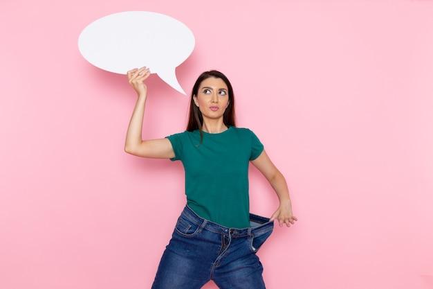 ピンクの壁に白い看板を保持している緑のtシャツの正面図若い女性ウエストスポーツ運動トレーニング美容スリムアスリート