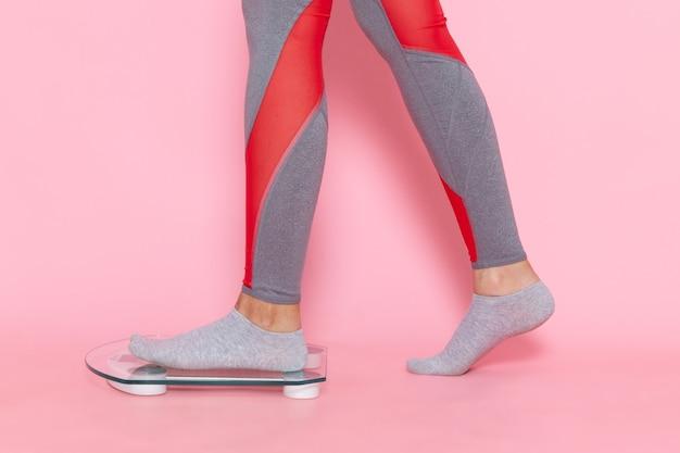 淡いピンクの壁のウエストエクササイズトレーニング美容スリムな女性のスポーツで彼女の体重を測定する緑のtシャツの正面図若い女性