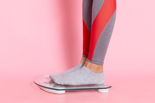 ピンクの壁のウエストスポーツ運動トレーニング美容スリムアスリートの体重を測定する緑のtシャツの正面図若い女性