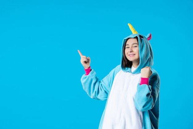 파란색 배경에 잠옷 파티를위한 kigurumi의 전면보기 젊은 여성 휴식 수면 늦은 재미있는 밤 게임 친구 꿈 컬러 만화 애니메이션