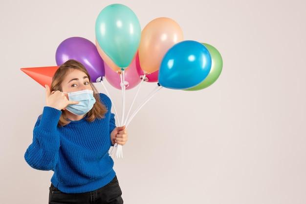 Вид спереди молодая женщина в маске, держащая разноцветные воздушные шары