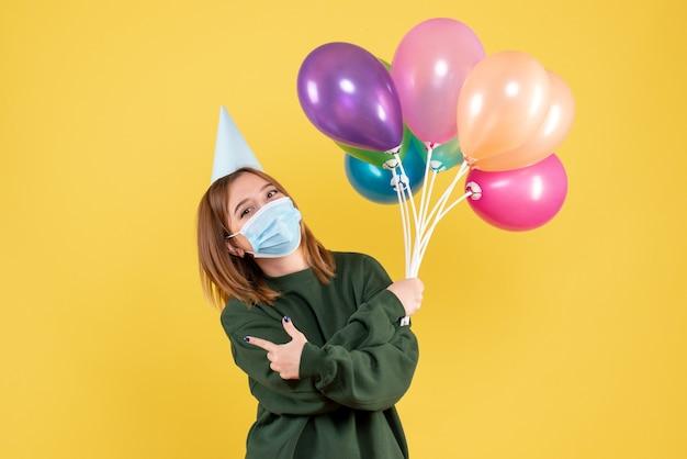 カラフルな風船を保持しているマスクの正面図若い女性