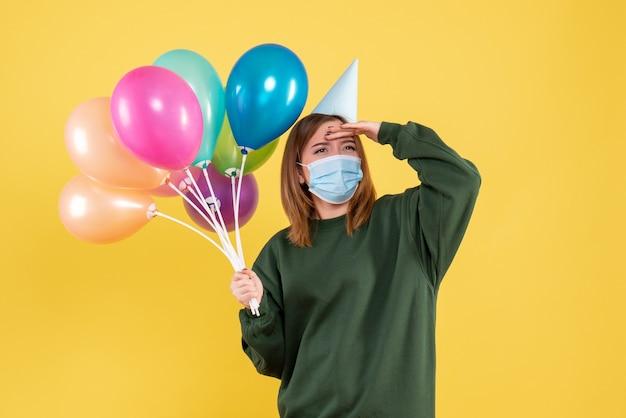 Вид спереди молодая женщина в маске, держащая разноцветные шары