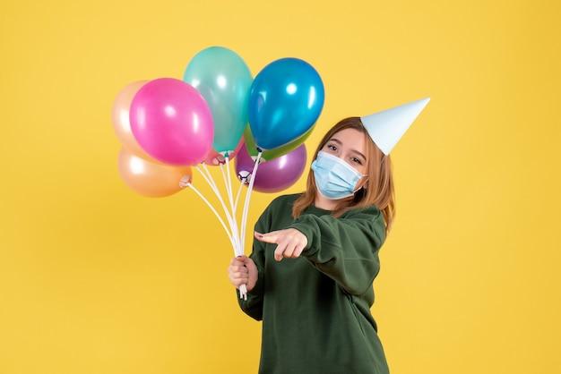 마스크 다채로운 풍선을 들고 전면보기 젊은 여성