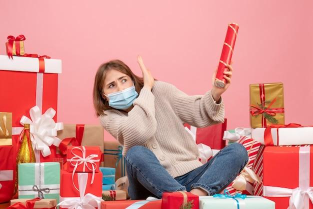 Вид спереди молодая женщина в маске сидит вокруг рождественских подарков