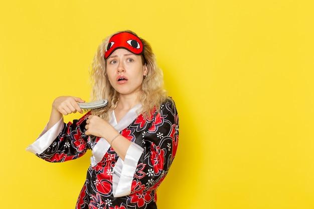 Вид спереди молодая женщина в ночном халате и в маске для глаз, расчесывающая волосы на желтой стене, спящая девушка, модель ночной кровати