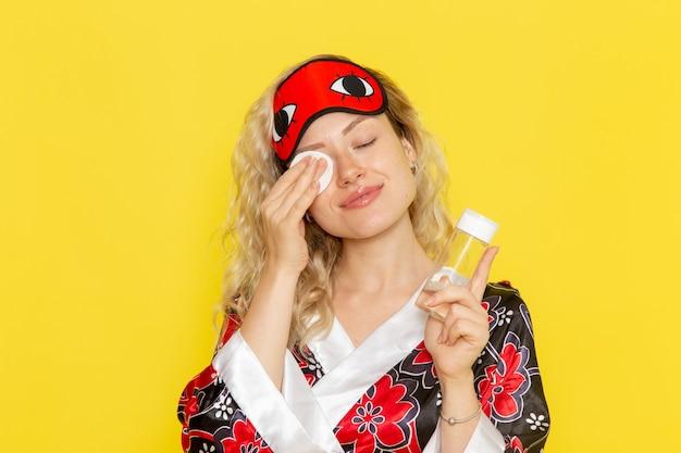 夜のローブと黄色の机の上の化粧から彼女の顔を掃除するアイマスクを身に着けている正面図若い女性睡眠女の子夜のベッドモデル