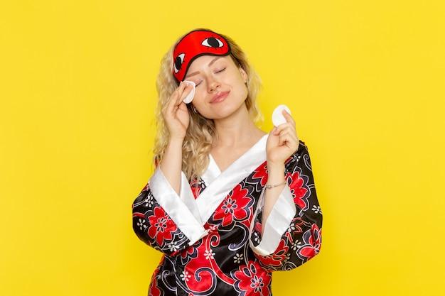夜のローブと黄色の壁の睡眠の女の子の夜のベッドモデルで彼女の顔を掃除するアイマスクを身に着けている正面図若い女性