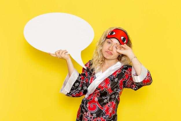 夜のローブと黄色の壁に大きな白い看板を保持しているアイマスクを身に着けている正面図若い女性睡眠少女ナイトベッドモデル