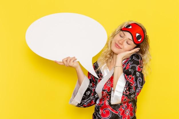 밤 가운에 전면보기 젊은 여성과 노란색 벽에 거대한 흰색 기호를 들고 눈 마스크를 착용 수면 밤 침대 모델 소녀 색상