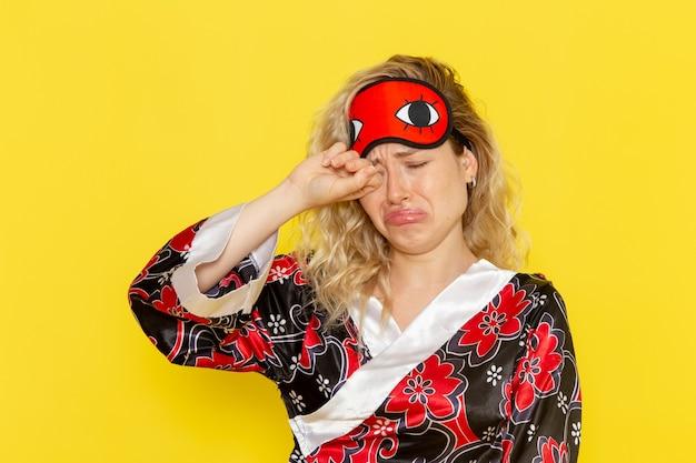 夜のローブで若い女性の正面図と明るい黄色の壁で偽の泣きを眠る準備をしているアイマスクを身に着けている女性モデルの夜のベッド