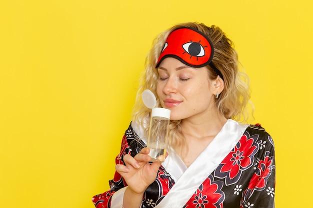夜のローブで若い女性の正面図と黄色の壁の睡眠の女性モデルの夜のベッドでフラスコの臭いを保持して眠る準備をしているアイマスクを身に着けている