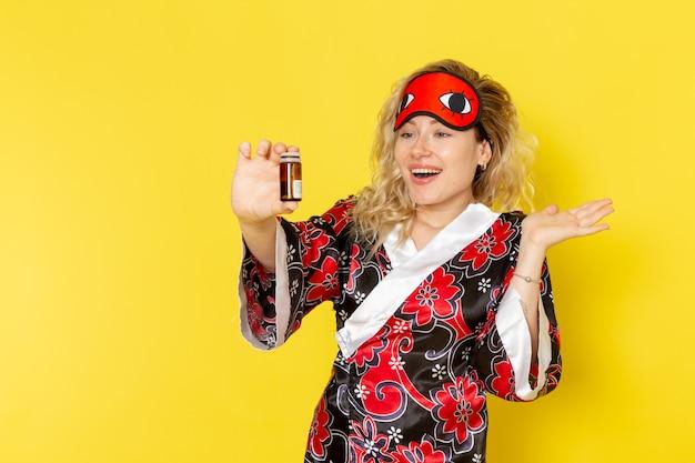 밤 가운에 전면보기 젊은 여성과 노란색 벽 수면 여성 어둠 모델 밤에 약을 들고 플라스크를 준비하는 아이 마스크를 착용