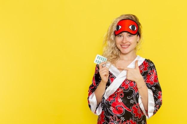 夜のローブで若い女性の正面図と黄色の壁に丸薬を保持して眠る準備をしているアイマスクを身に着けている女性の暗闇の色の夜