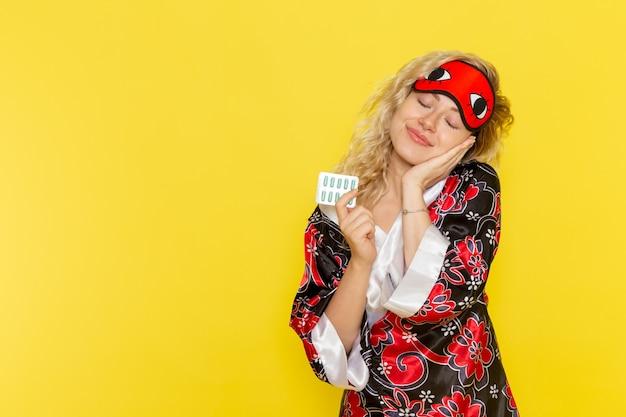 밤 가운에 전면보기 젊은 여성과 노란색 벽 수면 여성 어둠 모델 밤에 약을 들고 잠을 준비하는 아이 마스크를 착용