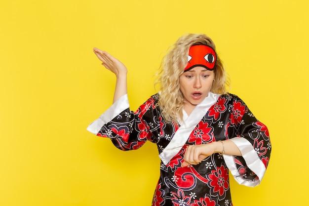 夜のローブで若い女性の正面図と薄黄色の壁の睡眠の女性モデルの夜のベッドで彼女の手首を見て眠る準備をしているアイマスクを身に着けている