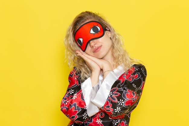 Вид спереди молодая женщина в ночном халате и в маске для глаз готовится ко сну на желтой стене ночной сон женский темный цвет