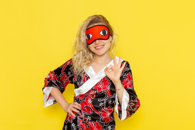 Вид спереди молодая женщина в ночном халате и в маске для глаз готовится ко сну, позирует и улыбается на желтой стене, спит женщина темнота цвет ночи