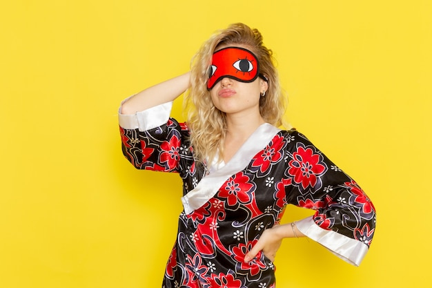 夜のローブで若い女性の正面図と明るい黄色の壁でポーズをとって眠る準備をしているアイマスクを身に着けている女性の闇モデルの夜