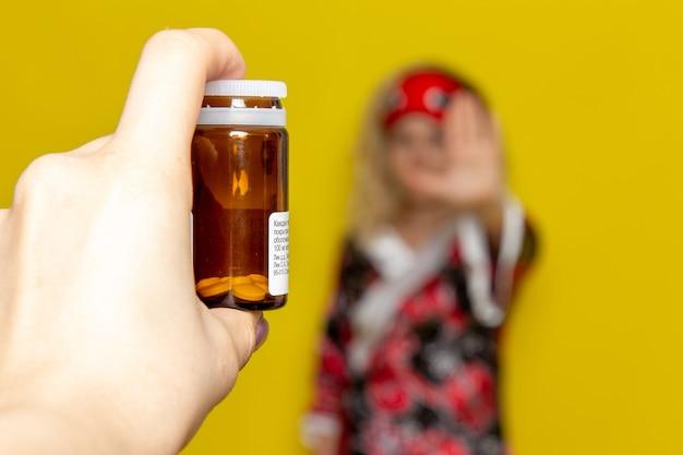 노란색 책상 수면 밤 침대 모델 색상에 최전선에 집중된 여성의 손에 약을 들고 밤 가운 아이 마스크의 전면보기 젊은 여성