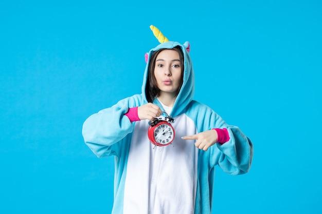 파란색 배경에 시계를 들고 잠옷 파티에서 전면 보기 젊은 여성 늦은 꿈 침대 악몽 여자 재미 밤 휴식 게임 시간